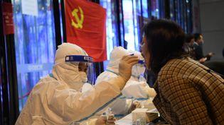Un travailleur médical prélève des échantillons sur un écouvillon sur un site de la ville de Lanzhou, dans la province de Gansu, le 21 octobre 2021. (FAN PEISHEN / XINHUA)