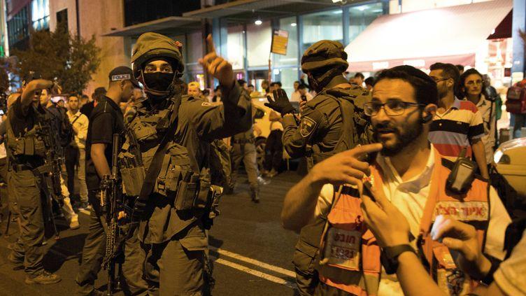 Un médecin et des membres des forces de sécurité israéliennes sur le site d'une attaque, à la gare routière de Jérusalem, mercredi 14 octobre 2015. (MENAHEM KAHANA / AFP)