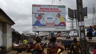 Des gens passent devant un panneau d'affichage à Yopougon, un quartier populaire d'Abidjan (la capitale économique) le 16 septembre 2020, pour promouvoir des élections pacifiques en Côte d'Ivoire prévues pour le mois d'octobre. (SIA KAMBOU / AFP)