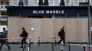 Des passants devant une boutique parisienne, le 17 décembre 2019. (FRANCOIS GUILLOT / AFP)