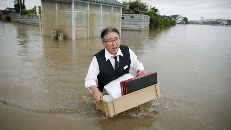 Un homme transporte des affairesà l'abri des inondationsà Oyama. Le typhon Etau a provoqué la crue de la rivière Omoigawa qui a chassé 100 000 personnes de leurs maisons,le 10 septembre 2015. (KYODO KYODO / REUTERS)