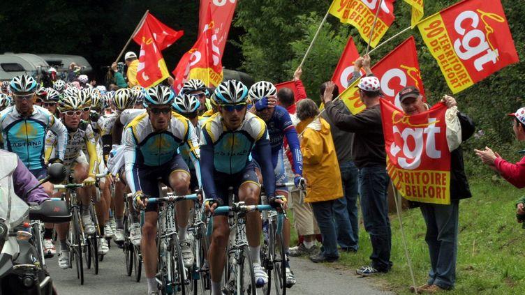 Des syndicalistes de la CGT brandissent des drapeaux lors du passage du Tour de France, dans le territoire de Belfort, le 18 juillet 2009. ( MAXPPP)