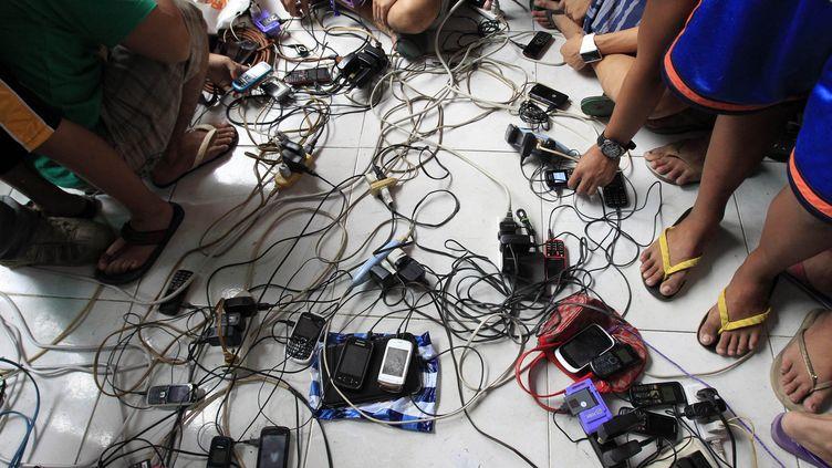 Des personnes chargent leurs téléphones après le passage du typhon Rallassun, à à Rosario (Philippine), le 18 juillet 2014. (ROMEO RANOCO / REUTERS)