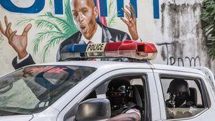 Des policier passent près d'un mur peint d'une fresque du président haïtien Jovenel Moise à Port-au-Prince (Haïti), le 15 juillet 2021. (VALERIE BAERISWYL / AFP)