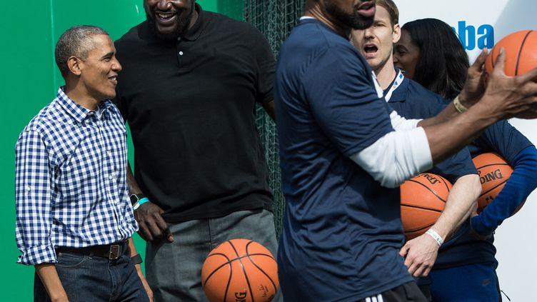 Dans cette photo d'archives prise le 28 mars 2016, le président américain Barack Obama plaisante avec l'ancien joueur de basket-ball de la NBA Shaquille O'Neal, reçu à la Maison Blanche à Washington. (NICHOLAS KAMM / AFP)
