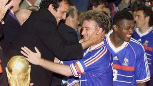 Michel Platini félicite Didier Deschamps, le capitaine de l'équipe de France,après la victoire des Bleus en finale de la Coupe du monde face au Brésil, le 12 juillet 1998. (GABRIEL BOUYS / AFP)