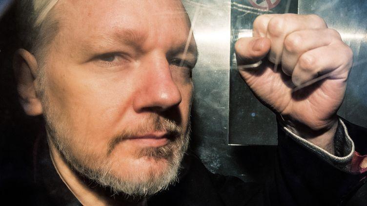 Julian Assange, le poing levé, dans le fourgon cellulairebritannique qui l'amène à une audience à Londres le 1er mai 2019. (DANIEL LEAL-OLIVAS / AFP)