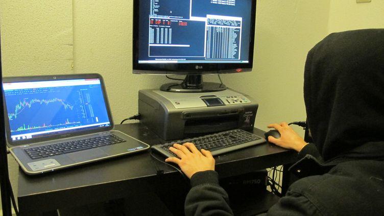 """Quentin, """"mineur"""" de monnaies virtuelles, vérifie le bon fonctionnement de son ordinateur. A sa gauche, le cours du bitcoin. (VINCENT MATALON / FRANCETV INFO)"""