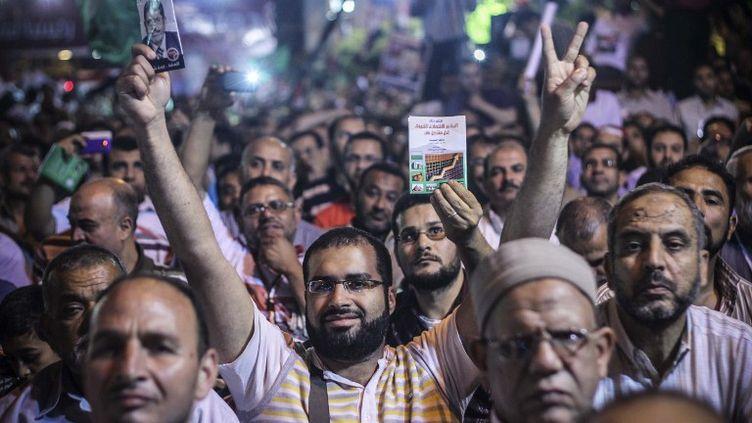 Des sympathisants des Frères musulmans brandissent la photo de Mohamed Morsi, le 20 mai 2012 au Caire (Egypte). (CITIZENSIDE.COM / AFP)