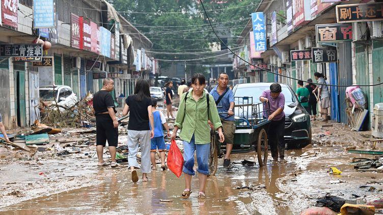 Une femme porte un sac dans une rue boueuse après les graves inondations et glissements de terrain qui ont touché ces derniers jours la ville de Gongyi, près de Zhengzhou, dans la province centrale du Henan, le 22 juillet 2021. (JADE GAO / AFP)