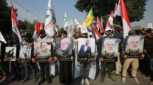 Des manifestants,le 4 janvier 2020,près de la zone verte de Bagdad en Irak, avecdes portraits des militaires tuéslors de l'assassinat du généralQassem Soleimani. (AHMAD AL-RUBAYE / AFP)