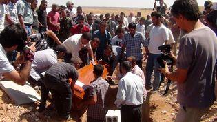 Les cercueils du petit Aylan Kurdi, de sa mère et de son grand-frère, en train d'être enterrés à Kobané (Syrie), le 4 septembre 2015. (ANHA / AFP)