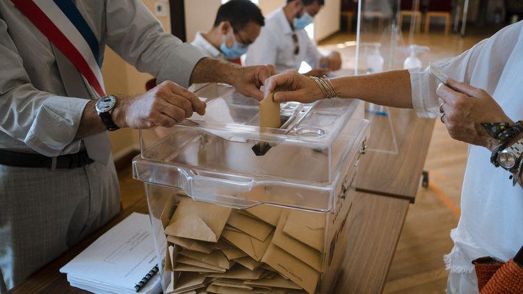 Une électrice vote pour les régionales et départementales à Corte, en Haute-Corse, le 27 juin 2021. (JEANNE FOURNEAU / HANS LUCAS / AFP)
