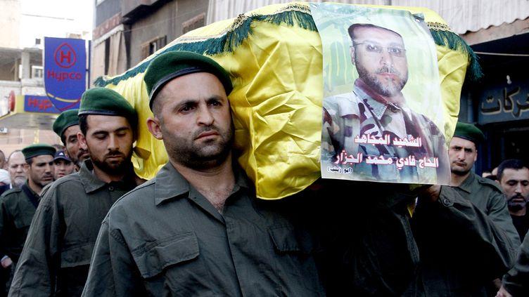 Des membres du Hezbollah transportent le cercueil d'un milicien tué lors des combats àQousseir, en Syrie,le 20 mars 2013, à Beyrouth (Liban). (STR / AFP)