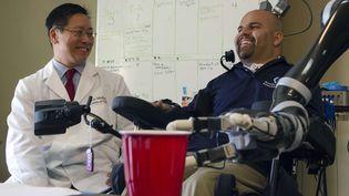 Erik Sorto (à droite), patient implanté avec une prothèse neuronale qui lui permet d'actionner son bras artificiel par la pensée, à Pasadena (Californie, Etats-Unis), le 14 avril 2015. (LANCE HAYASHIDA / AP / SIPA)