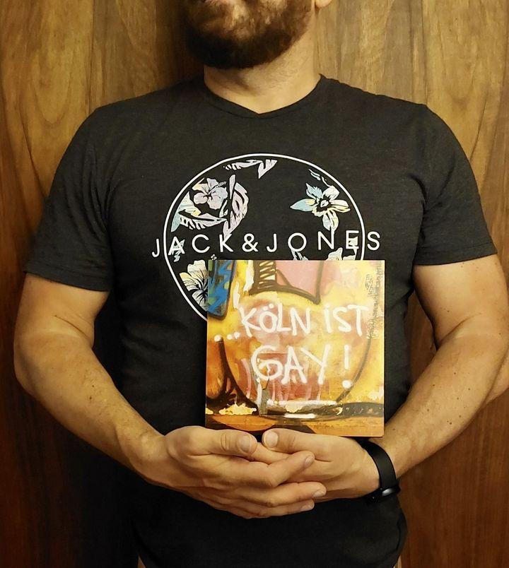 """Csaba, chez lui à Cologne (Allemagne), le 6 juillet 2021, avec une image où il est écrit """"Cologne est gay"""". (CSABA)"""