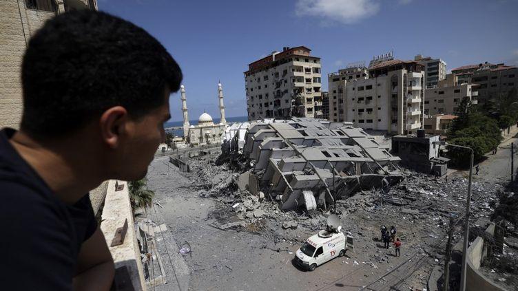 Un Palestinien observe les restes d'un immeuble détruit par des frappes israéliennes à Gaza, le 12 mai 2021. (MOHAMMED ABED / AFP)