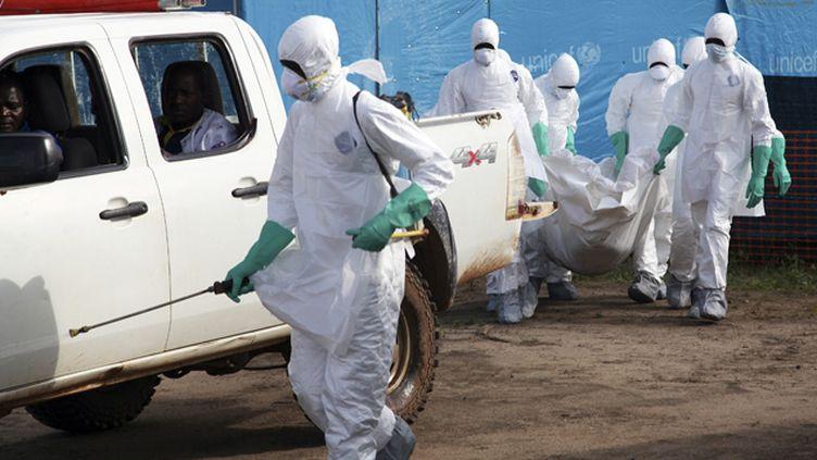 (Au Liberia, des hommes enlèvent le corps d'une femme morte d'Ebola © MaxPPP/ EPA/ Ahmed Jallanzo)