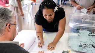 Une femme vote pendant le deuxième referendum sur l'indépendance de la Nouvelle-Calédonie en octobre 2020. (THEO ROUBY / AFP)