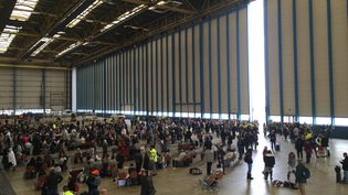 Despassagers sont assis bloqués dans un hangar à l'aéroport de Zaventem, le 22 Mars, 2016, après les attentats terroristes de Bruxelles (CITIZENSIDE / FABRICE DEKONINCK / AFP)