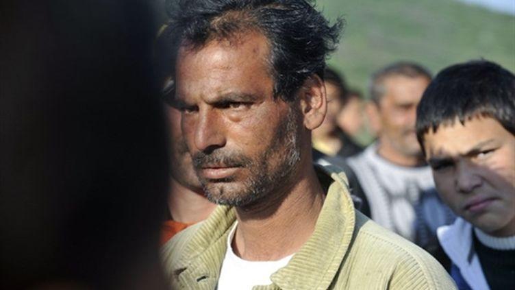 Un homme rom regarde les femmes et les enfants de sa communauté quitter le village de Gyöngyöspata (AFP - ATTILA KISBENEDEK)