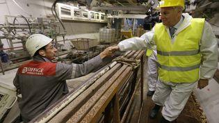 Jean-Marc Ayrault (à droite) salue un ouvrier qui travaille sur le chantier d'un tramway, mardi 13 août 2013 à Vélizy-Villacoublay (Yvelines). (KENZO TRIBOUILLARD / AFP)