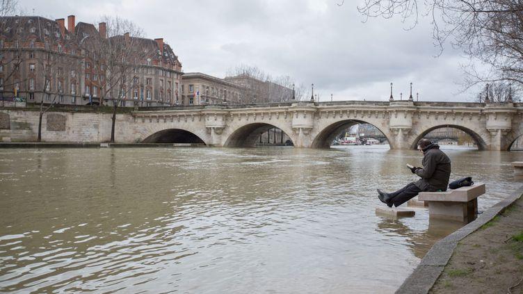 Un homme lit sur un banc pendant la crue de la Seine, le 25 janvier 2018, à Paris. (MAXPPP)