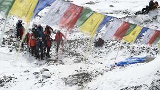 Des secouristes transportent une personne blessée au camp de base de l'Everest, samedi 26 avril 2015. (ROBERTO SCHMIDT / AFP)