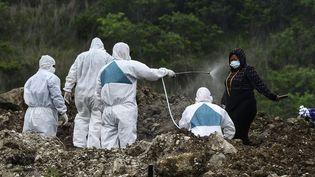 Uneéquipe envoiedu produit désinfectant surune femme,lors de l'enterrement d'une victime présumée du coronavirus dans un cimetière de Tegucigalpa (Honduras), le 21 juin 2020. (ORLANDO SIERRA / AFP)