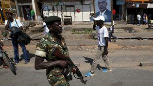Un militaire patrouille alors qu'un partisan du président burundais Pierre Nkurunziza promène son portrait, le 15 mai 2015, dansune rue de la capitale Bujumbura (Burundi). (GORAN TOMASEVIC / REUTERS)