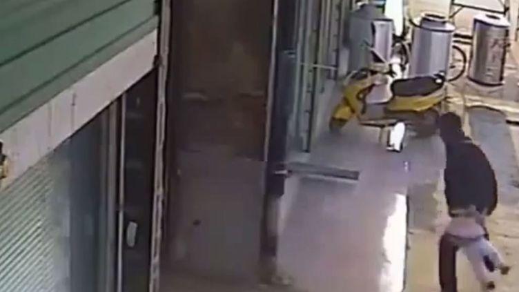 Capture d'écran où l'on voit un homme jeter un bébé en l'air à Huainan (Chine). ( YOUTUBE)