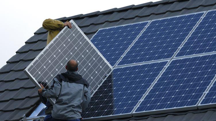 Un homme installe des panneaux photovoltaïques sur une maison, le 3 mai 2015, en Moselle. (THIERRY GRUN / ONLY FRANCE / AFP)