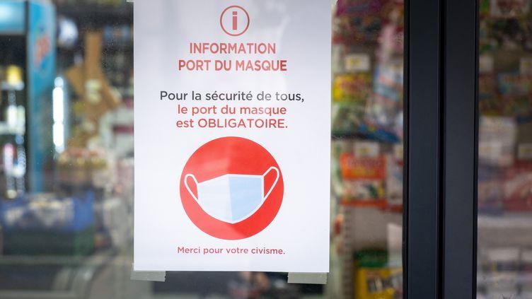 Une affichette rappelle l'obligation du port du masque de protection sanitaire, sur la vitrine d'un magasin à Toulouse, le 15 octobre 2020. (ADRIEN NOWAK / HANS LUCAS)