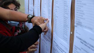 Des lycéens regardent les résultats du bac, à Saint-Denis (La Réunion), le 6 juillet 2021. (RICHARD BOUHET / AFP)