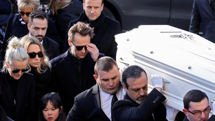 """La femme et les enfants de Johnny Hallyday suivent le cercueil de """"l'idole des jeunes"""" à l'entrée de l'église de la Madeleine, accompagnés par Emmanuel et Brigitte Macron, le 9 décembre 2017 à Paris. (LUDOVIC MARIN / AFP)"""