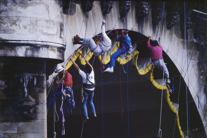 Des alpinistes attachent la toile hissée sous l'une des arches du Pont Neuf (© Christo 1985 Photo © Wolfang Volz)
