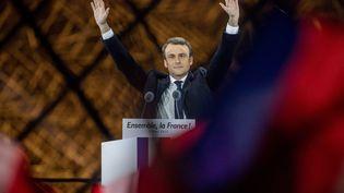 Emmanuel Macron lève les bras le soir du 7 mai, devant la pyramide du Louvre, à Paris, après sa victoire à la présidentielle. (MICHAEL KAPPELER / DPA)