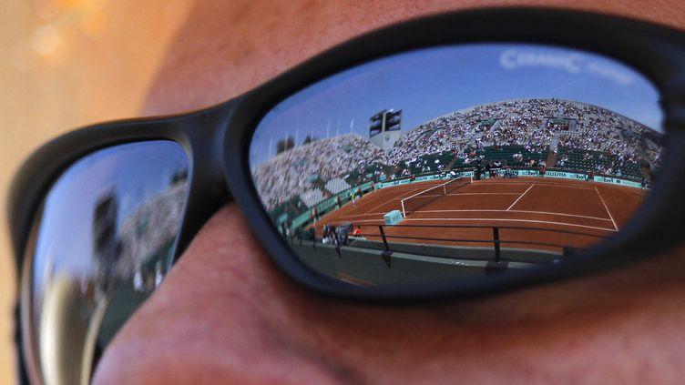 Roland-Garros se reflète dans les lunettes d'un spectateur, le 27 mai 2012. (PATRICK KOVARIK / AFP)