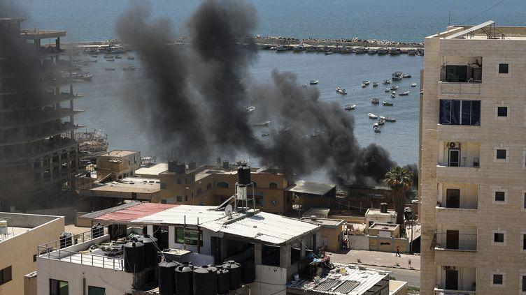 Des panaches de fumée noire s'élèventaprès une frappe aérienne israélienne sur le port maritime de la ville de Gaza, le 14 mai 2021. (MAHMUD HAMS / AFP)