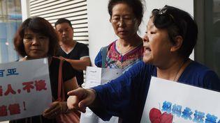 Des proches de passagers du vol MH370 réclament des explications devant le siège chinois de Malaysia Airlines, à Pékin (Chine), le 6 août 2015. (GREG BAKER / AFP)