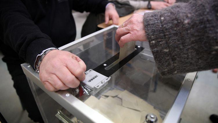 Un électeur place son bulletin dans l'urne à Lille (Nord), le 29 mars 2015. (THIERRY THOREL / CITIZENSIDE.COM / AFP)