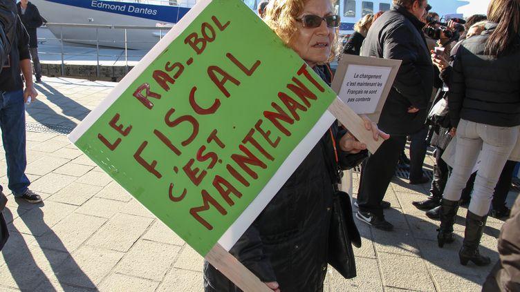 A Marseille (Bouches-du-Rhône), une manifestante exprime son mécontentement à l'encontre de la politique fiscale de François Hollande, le 1er décembre 2013. ( DENIS THAÜS / CITIZENSIDE / AFP)