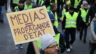 """Un """"gilet jaune"""" tient une pancarte sur laquelle il est écrit """"médias = propagande d'Etat"""", le 12 janvier 2019, à Paris. (LUDOVIC MARIN / AFP)"""