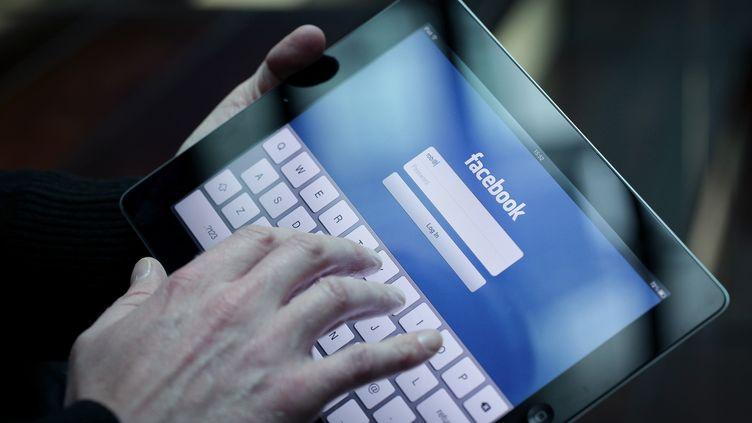 Un homme ouvre Facebook sur un iPad, le 14 mai 2012. (JASON ALDEN / BLOOMBERG / GETTY IMAGES)