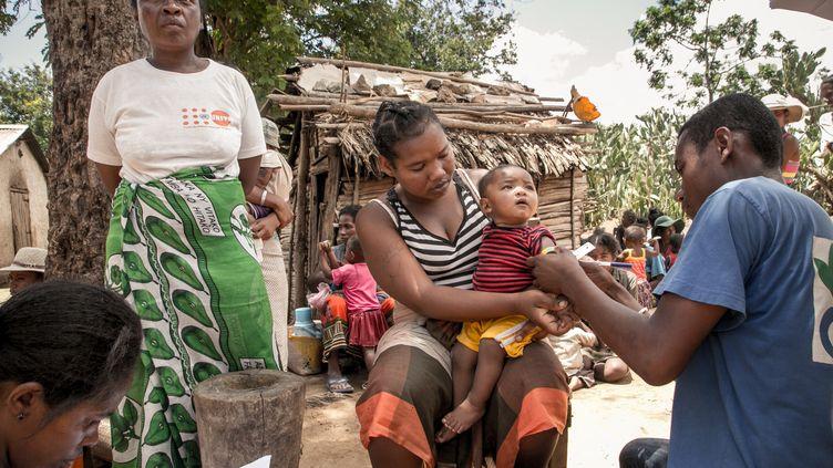 Un membre d'Action contre la faim mesure le bras d'un enfant pour détecter une possible malnutrition, àItofaka (Madagascar), le 14 décembre 2018. (RIJASOLO / AFP)