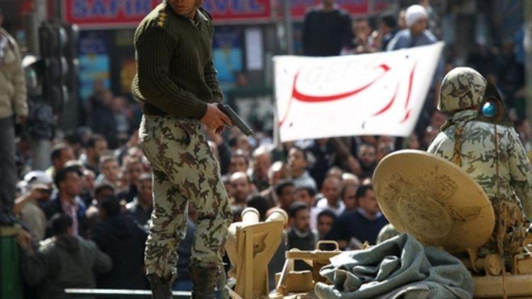 Un soldat égyptien tente de disperser des manifestants en colère pour protéger un policier place Tahrir au Caire, lundi (AFP PHOTO / KHALED DESOUKI)