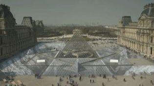 L'œuvre de l'artiste JR, un collage en trompe-l'œil donnant l'impression que le sol s'ouvre sous la pyramide du Louvre. (FRANCE 2)