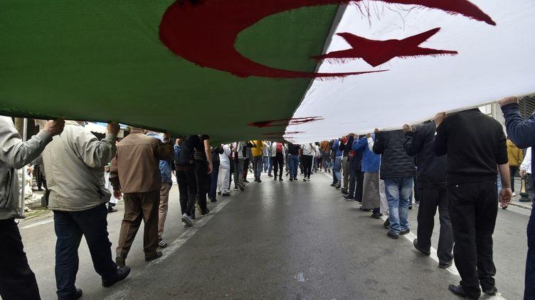 Des Algériens déploient un drapeau national géant lors d'une manifestation anti-gouvernementaleà Alger, le 2 avril 2021. (RYAD KRAMDI / AFP)