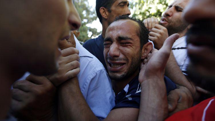 Des Palestiniens pleurent la mort de leurs proches dans des affrontements avec des soldats israéliens, en Cisjordanie, le 26 août 2013. (MOHAMAD TOROKMAN / REUTERS)
