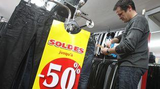Un homme prépare les soldes d'hiver dans un magasin de vêtements à Hirson (Aisne), le 10 janvier 2012. (FRED HASLIN / LE COURRIER PICARD / MAXPPP)